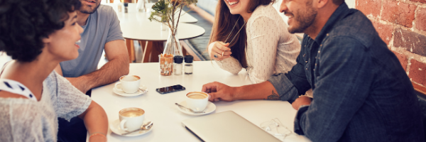 group of 4 sitting with coffee drinks during work