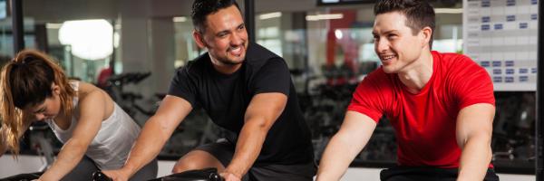 Two men on stationary bikes smiling