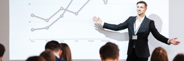 man presenting in front of line graph