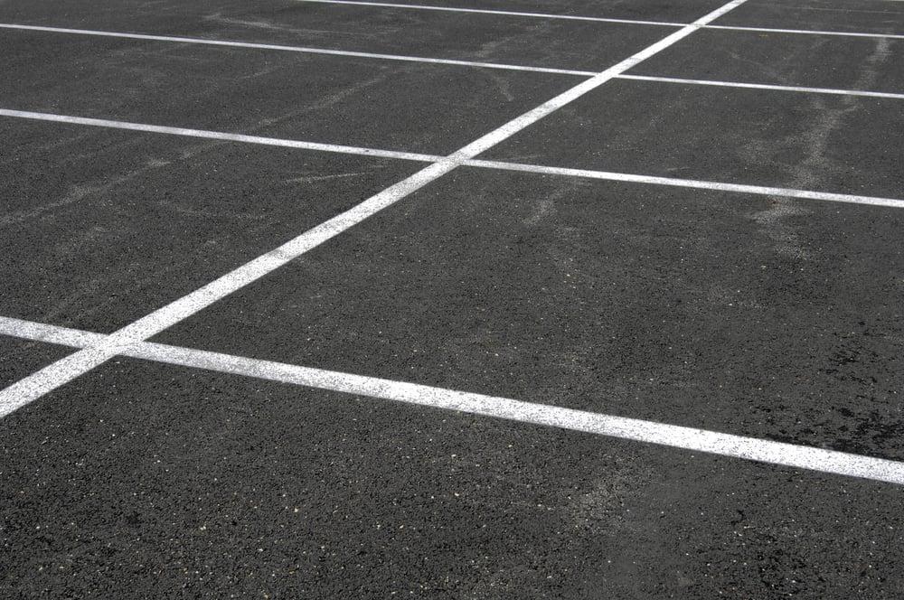 Grid of white lines on weathered asphalt parking lot
