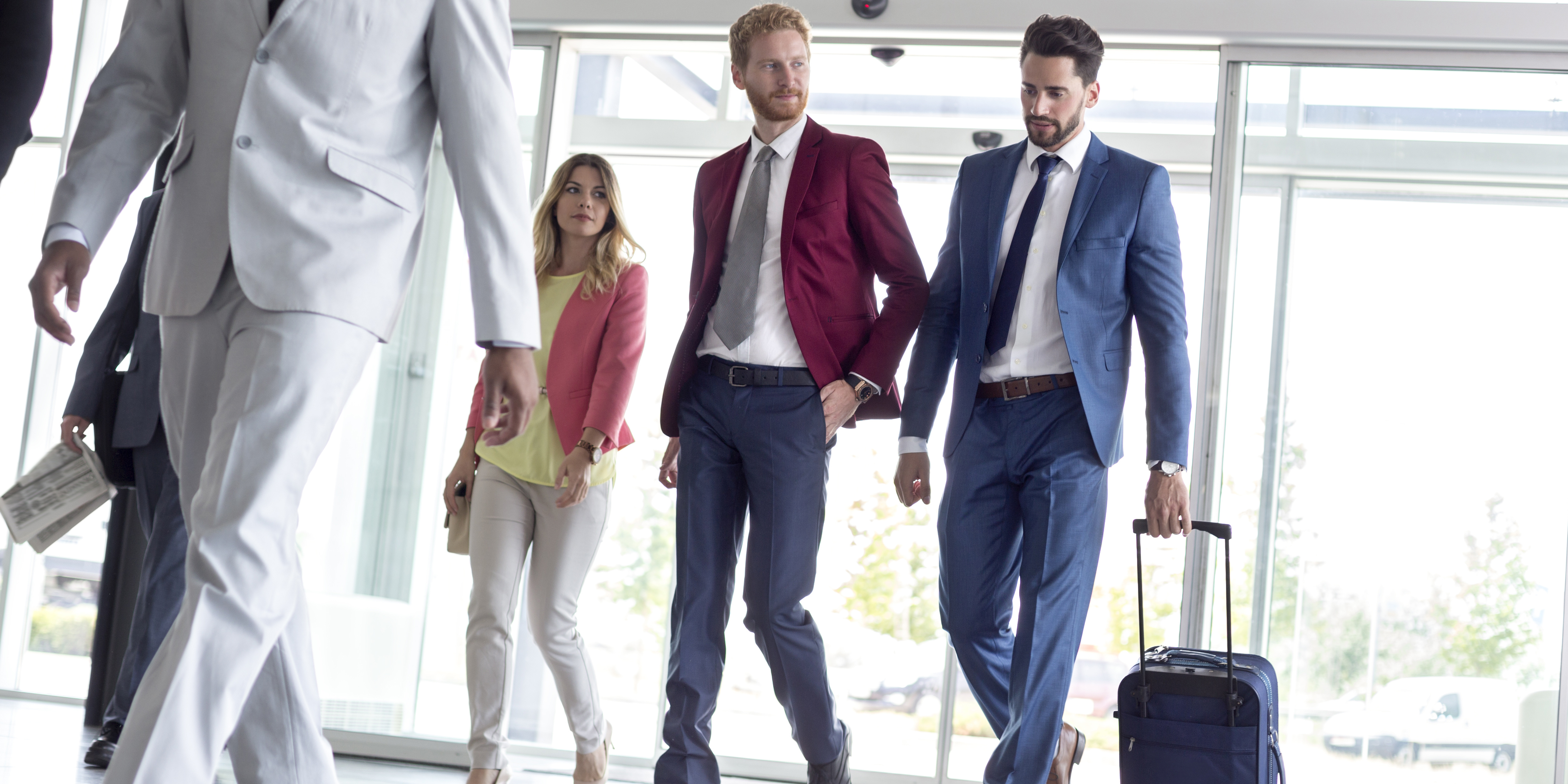 two businessmen arriving at airport with luggage