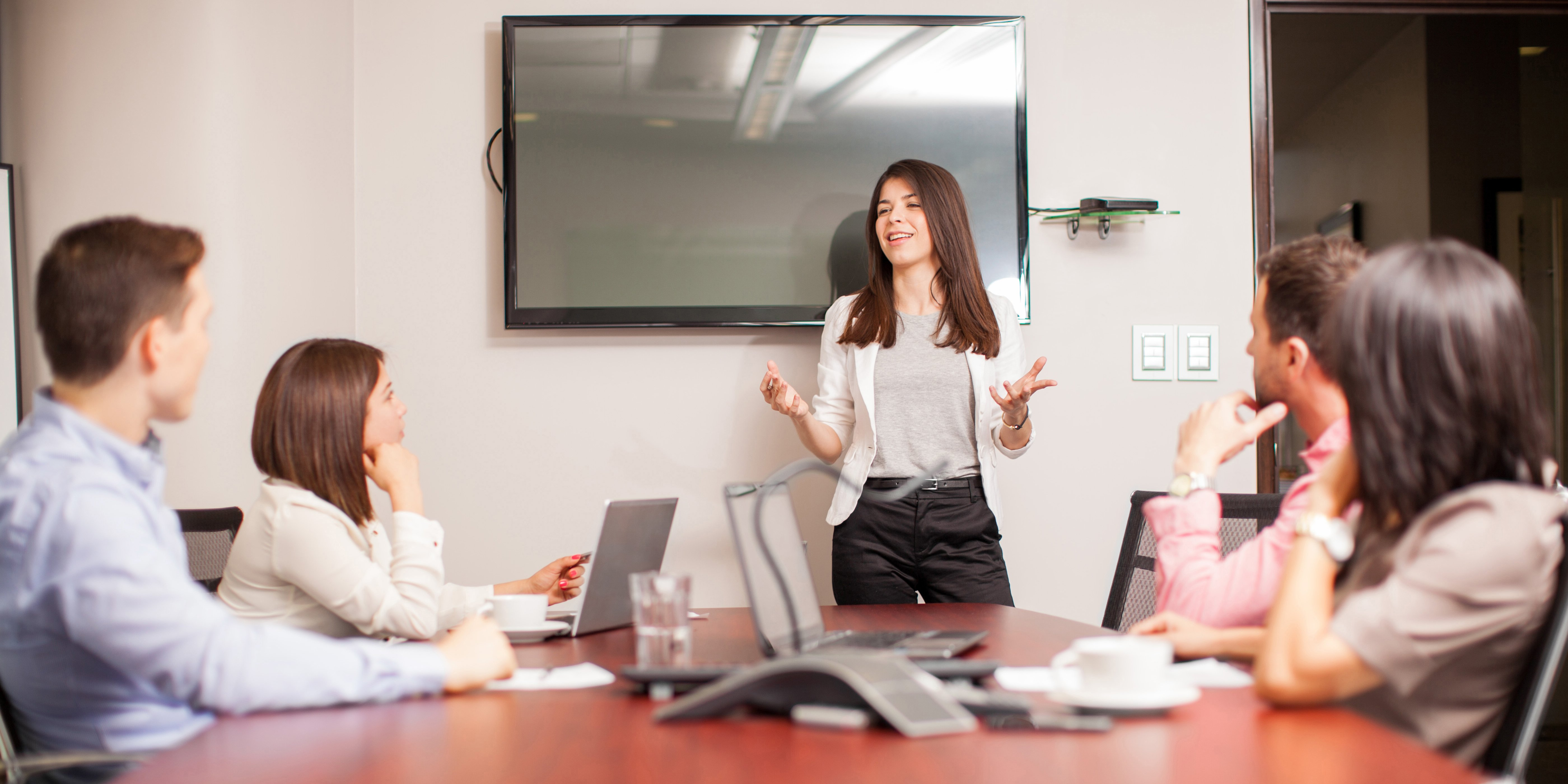 woman presenting to coworkers in conference room